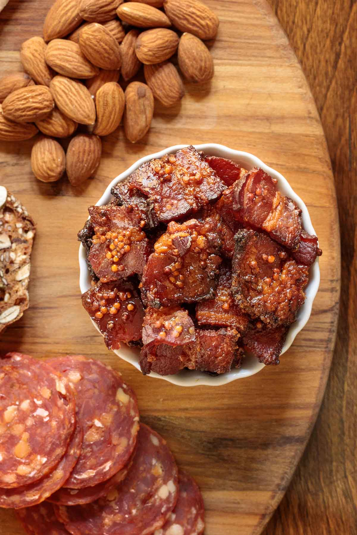Overhead closeup photo of a bowl of Maple Mustard Candied Bacon on a wood appetizer board surrounded by nuts, crackers and sausage.