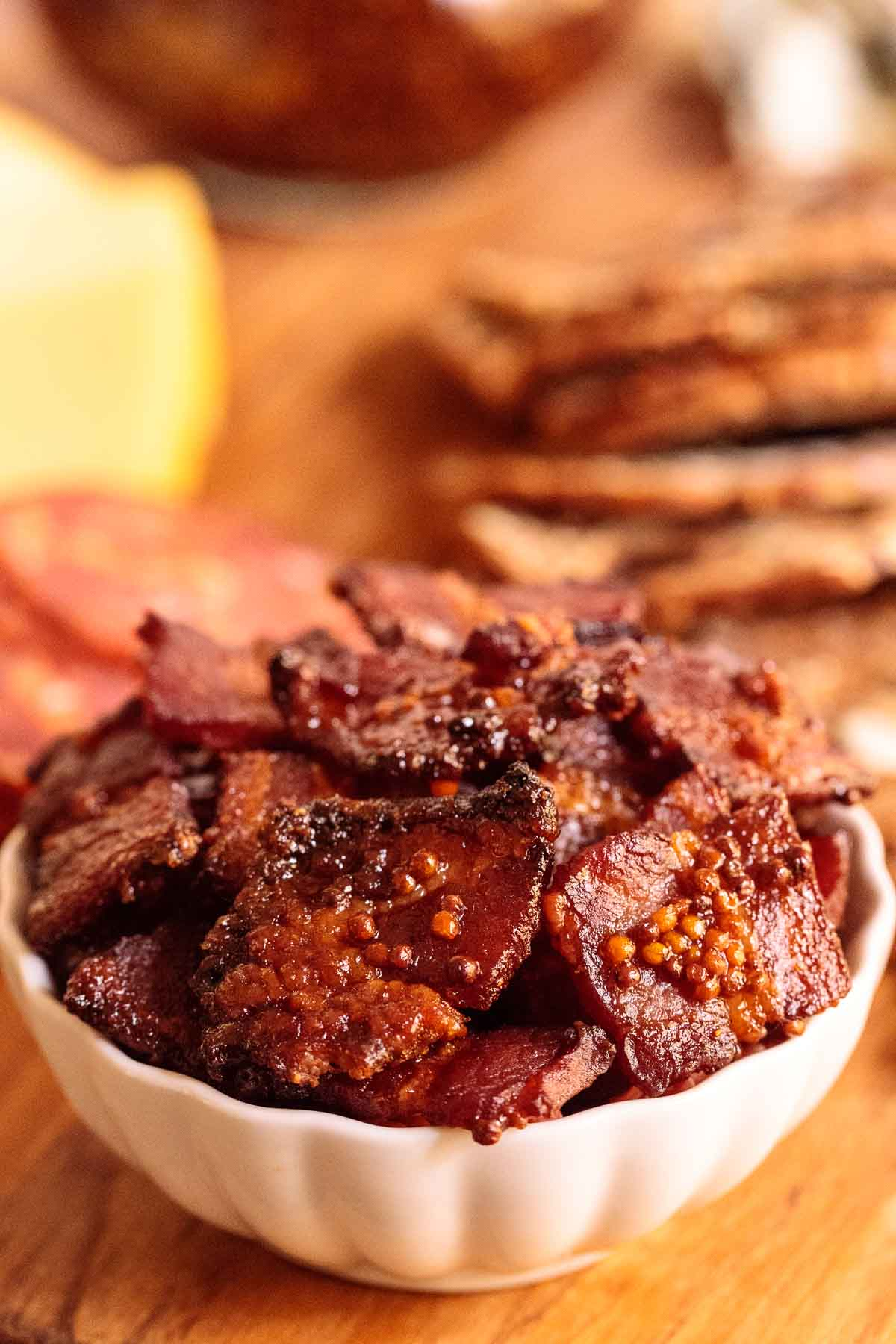 Closeup photo of a small bowl of Maple Mustard Candied Bacon on a cheese board.