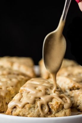 Close up vertical picture of Maple Pecan Scones on a platter with a spoon drizzling glaze over top