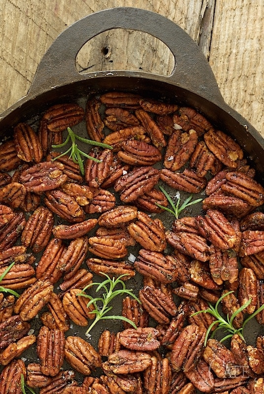 Vertical closeup photo of Maple and Rosemary Brown Butter Pecans in an oval cast iron pan.