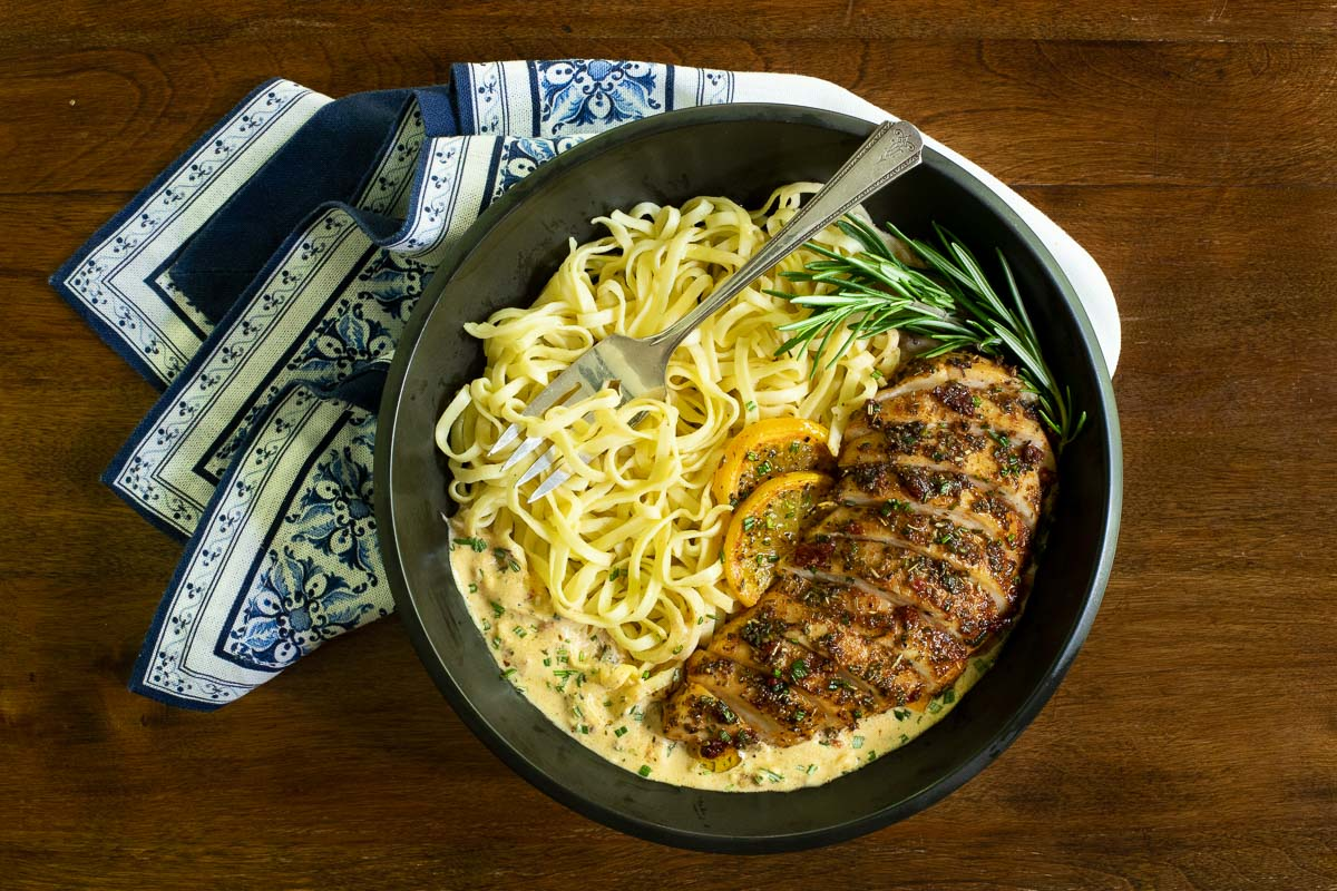 Overhead horizontal photo of a black serving bowl with Marry Me Chicken and fresh pasta with lemons and rosemary sprigs as garnish.