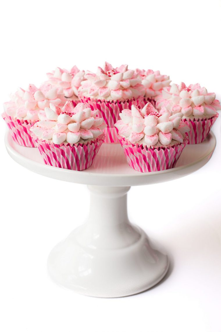 Vertical picture of poinsettia cupcakes in pink wrappers on a white cake stand