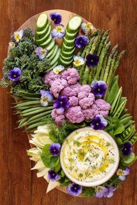 Vertical overhead photo of a veggie platter featuring Mediterranean Lemon Feta Dip on an oval wood appetizer platter.