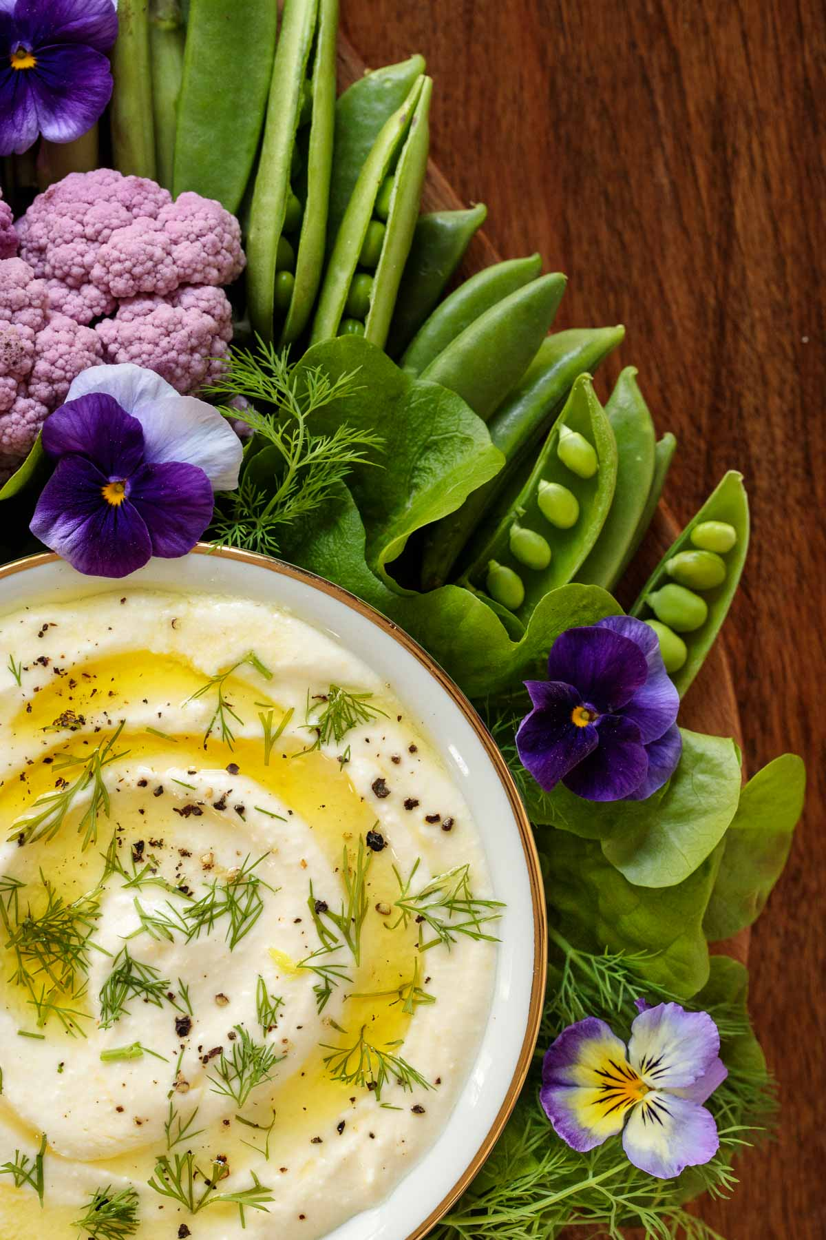 Overhead closeup photo of a Mediterranean Lemon Feta Dip surrounded by vegetables and edible flowers.