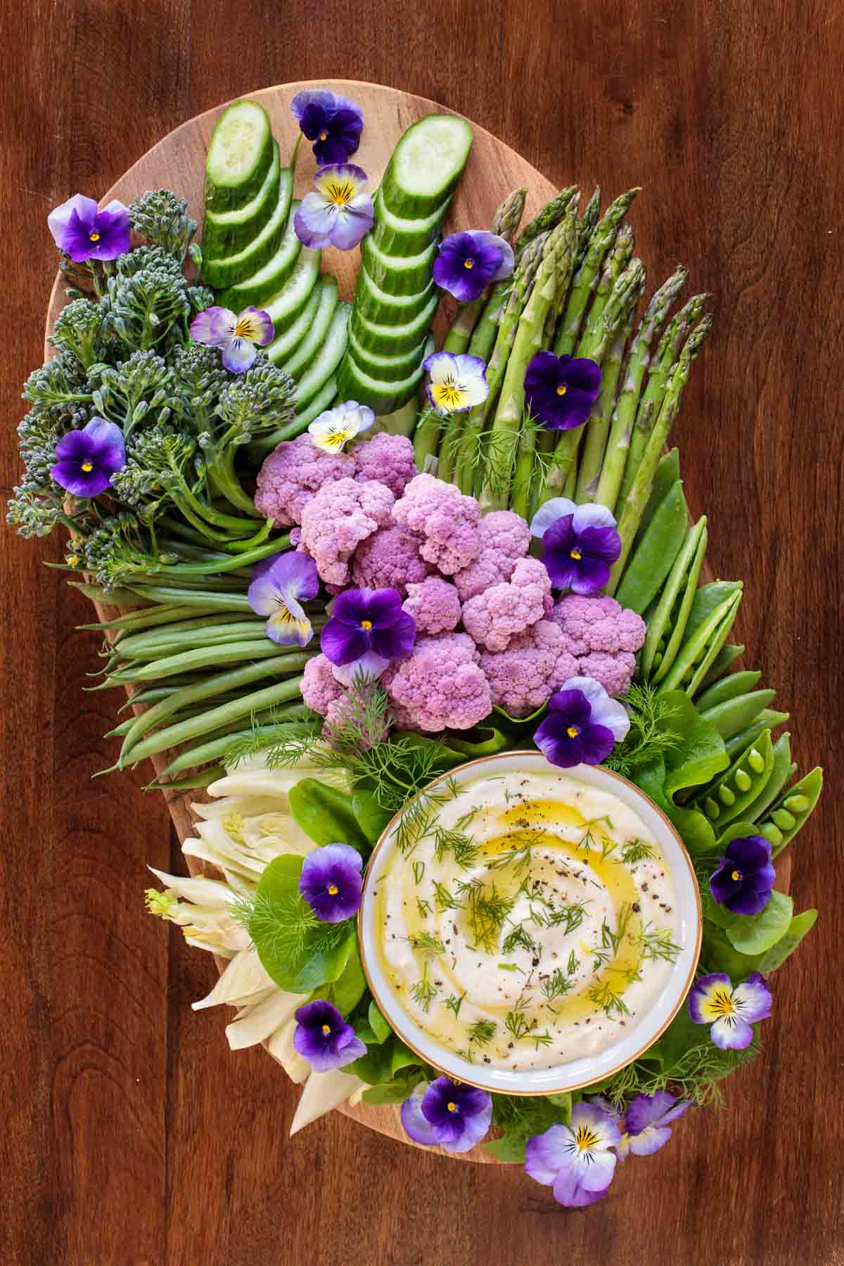 Overhead picture of feta dip surrounded by fresh vegetables on an oval platter
