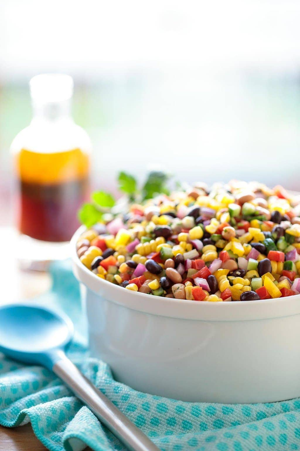 Photo of a white serving bowl of Mexican Bean Salad on a turquoise cloth with a glass jar of dressing in the background.