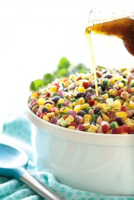 Vertical picture of Mexican Corn and Bean Salad in a white bowl with dressing being poured on top