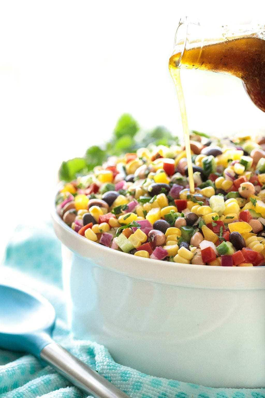 Vertical photo of Mexican Corn and Bean Salad in a white bowl with dressing being poured on top. The bowl is resting on a turquoise patterned cloth.