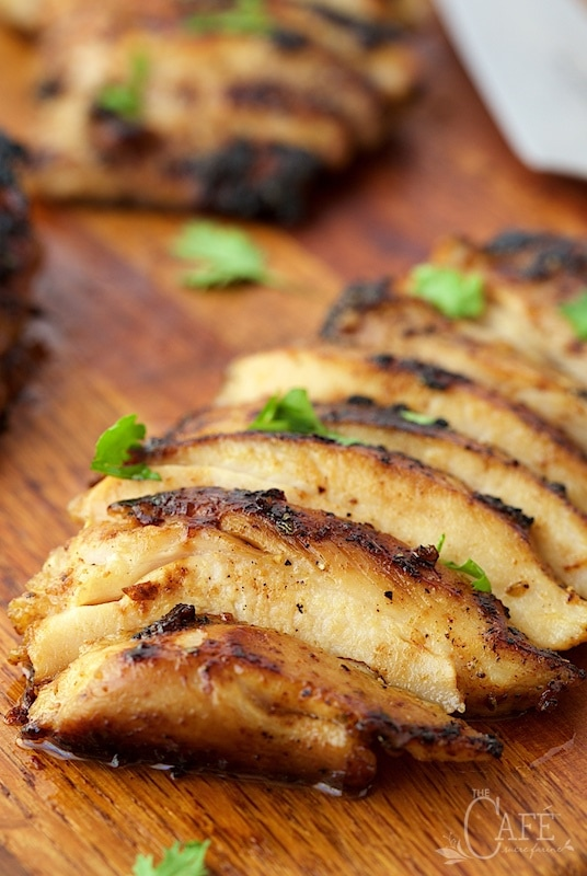 Closeup shot of slices of Mexican Honey-Lime Grilled Chicken on a wood cutting board.