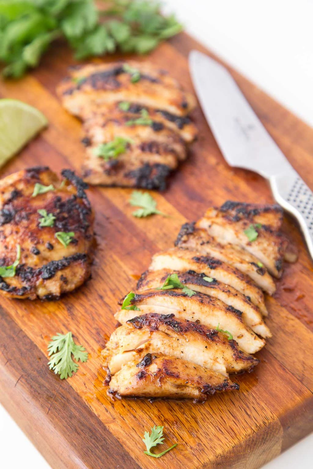 Closeup photo of Mexican Honey-Lime Grilled Chicken on a wood cutting board with lime wedges and chopped cilantro as a garnish