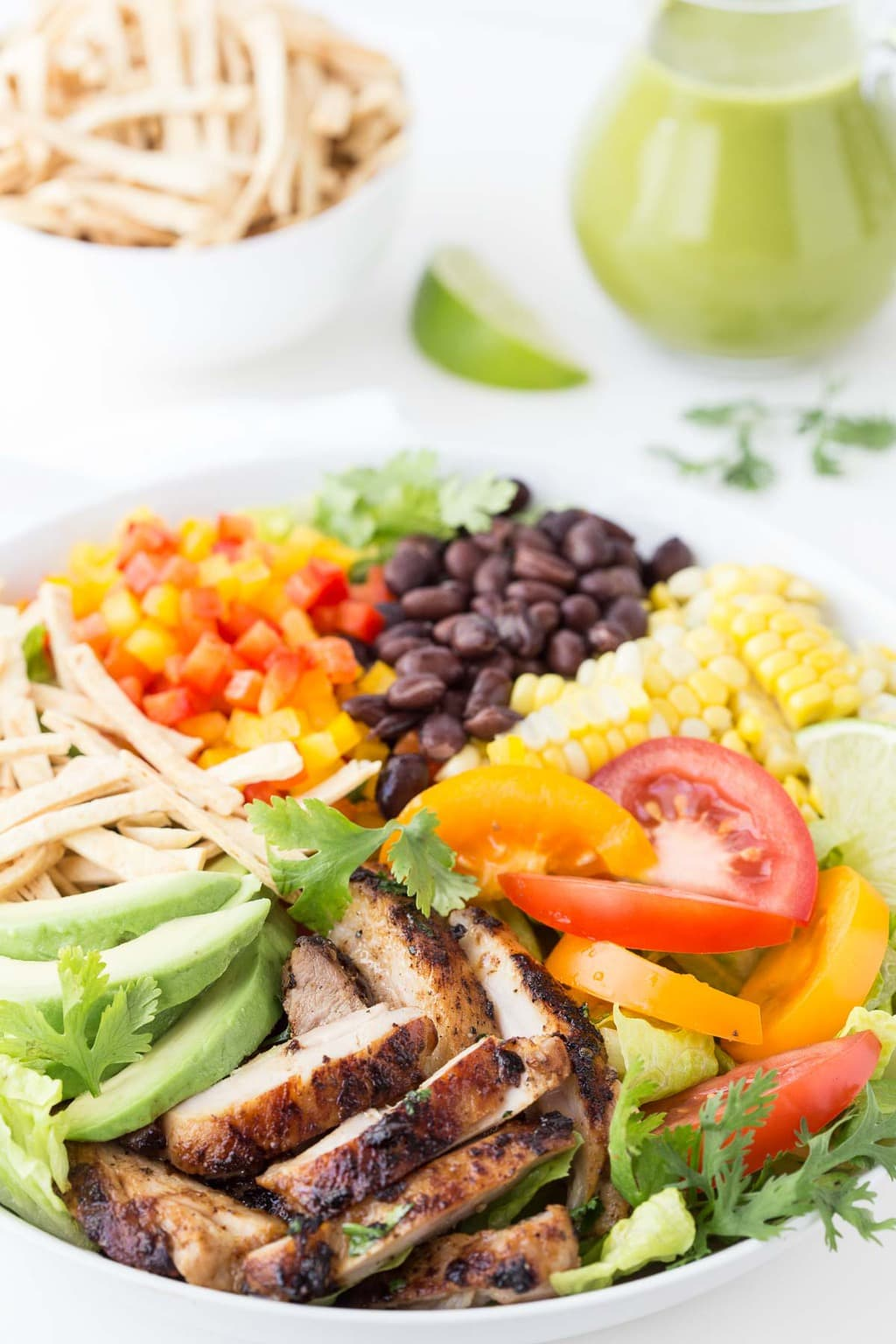 Vertical picture of Mexican Grilled Chicken Salad with dressing beside it.