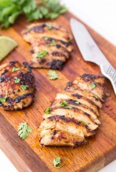 Vertical picture of Mexican Grilled Chicken sliced on a wooden cutting board
