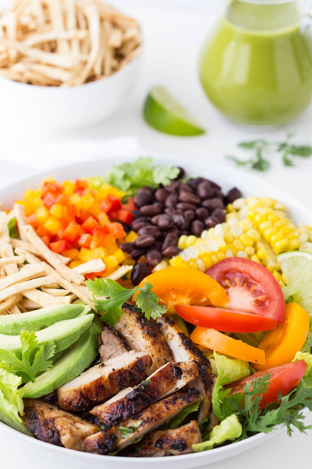 Vertical picture of mexican grilled chicken salad in a white bowl