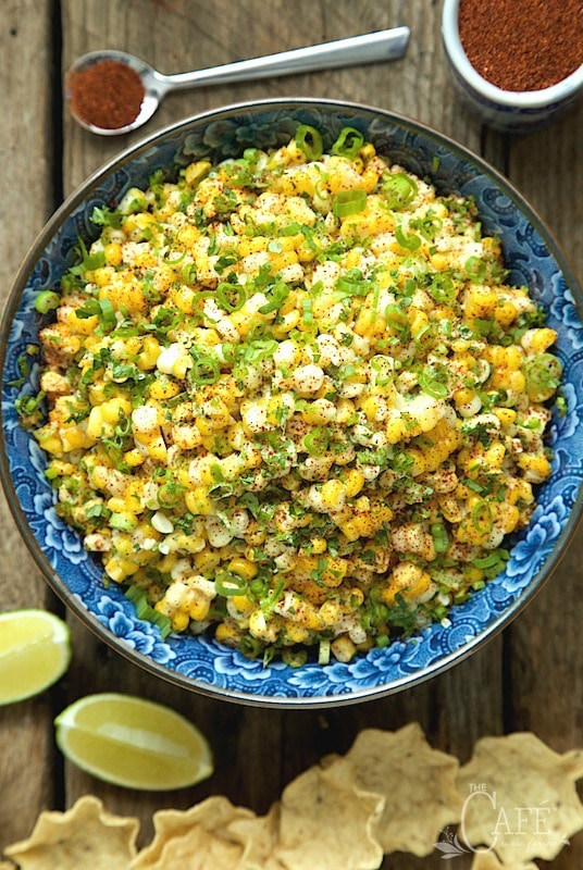 Vertical Image of Mexican Street Corn in a blue and white bowl with lime wedges for garnishes and chips for serving.