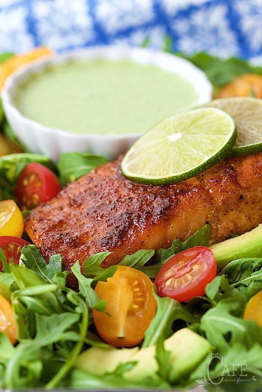 Photo of a plate of Mexican Sugar-Seared Salmon Salad with a bowl of dressing in the background and salmon with lime garnish in the center of the photo.