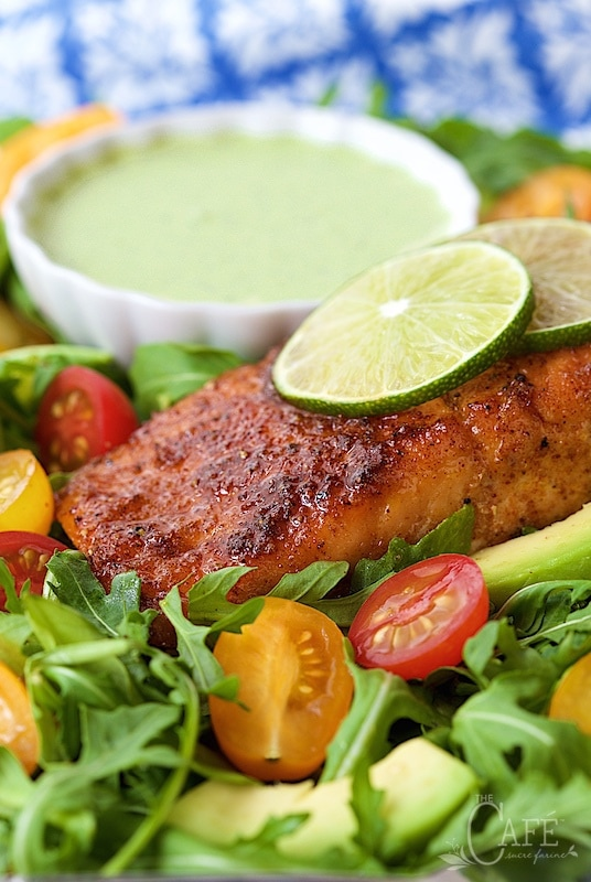 A vertical image of a Mexican Sugar Seared Salmon Salad on a plate with dressing and lime garnishes.