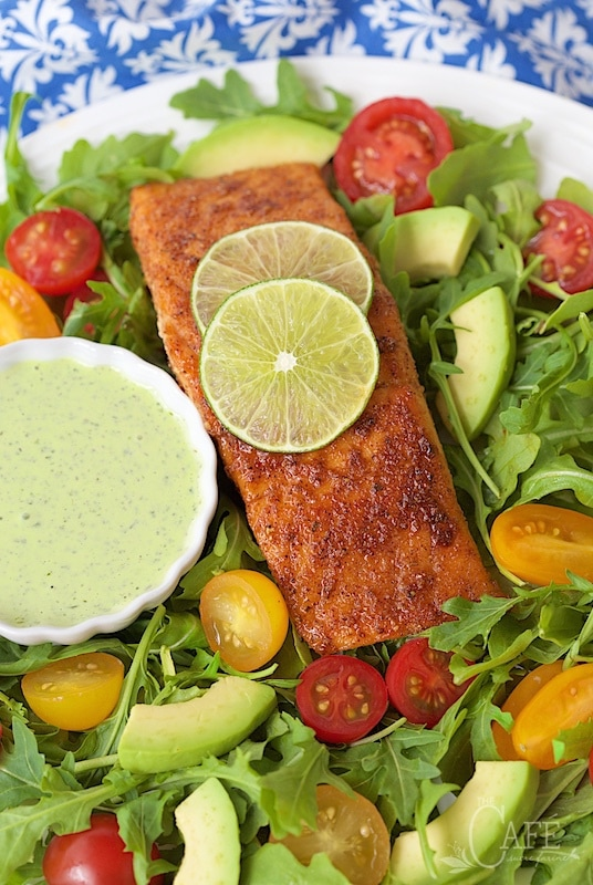 Photo of a plate of Mexican Sugar-Seared Salmon Salad with a small bowl of Spicy Cilantro Buttermilk Dressing.
