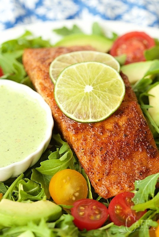 Photo of a plate of Mexican Sugar-Seared Salmon Salad with a bowl of Spicy Cilantro Buttermilk dressing center left and a salmon fillet center right garnished with lime slices.