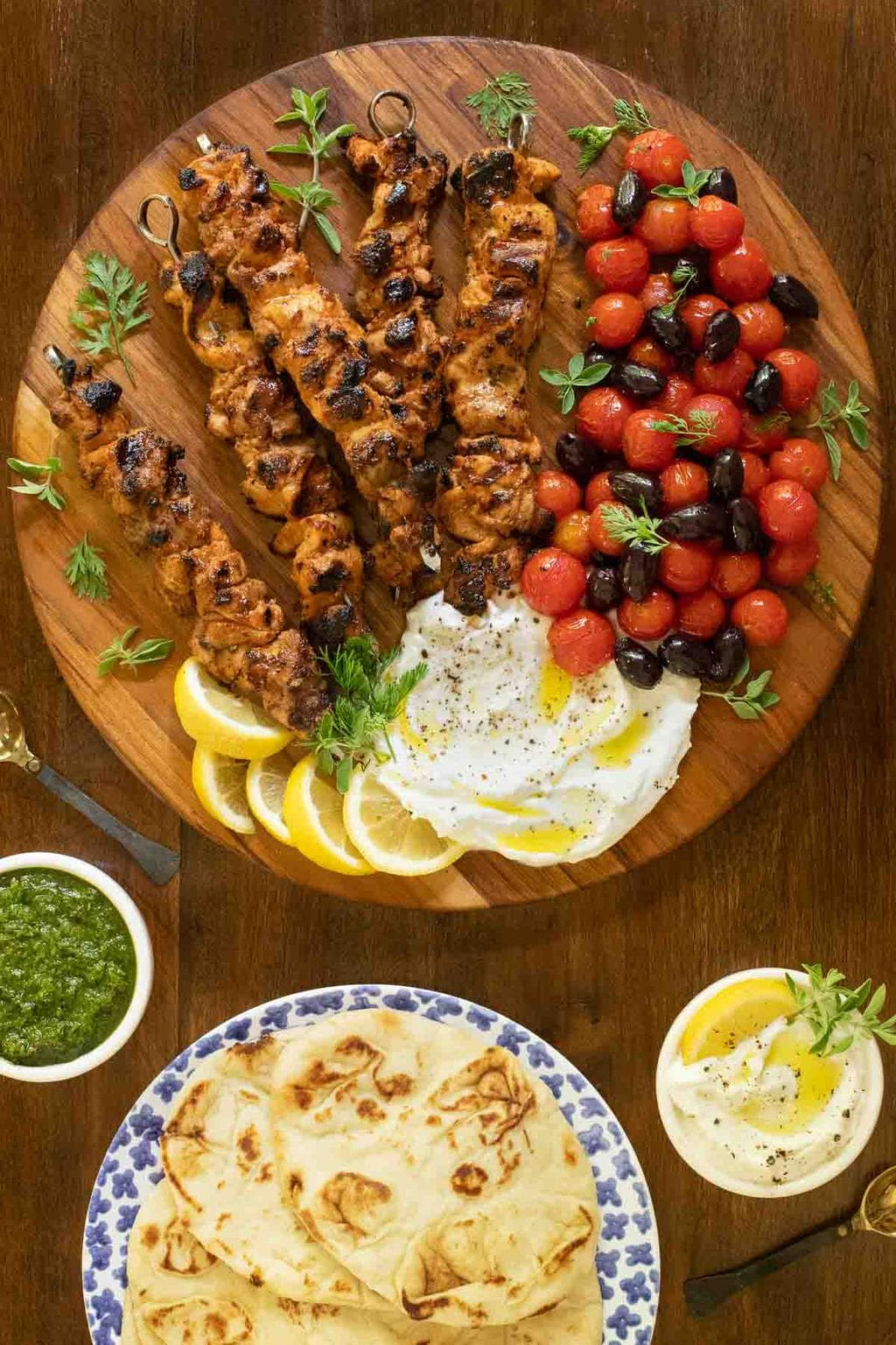 Overhead vertical photo of Middle Eastern Chicken with Toum on a round wood cutting board with lemon wedges, zhung and cherry tomatoes.