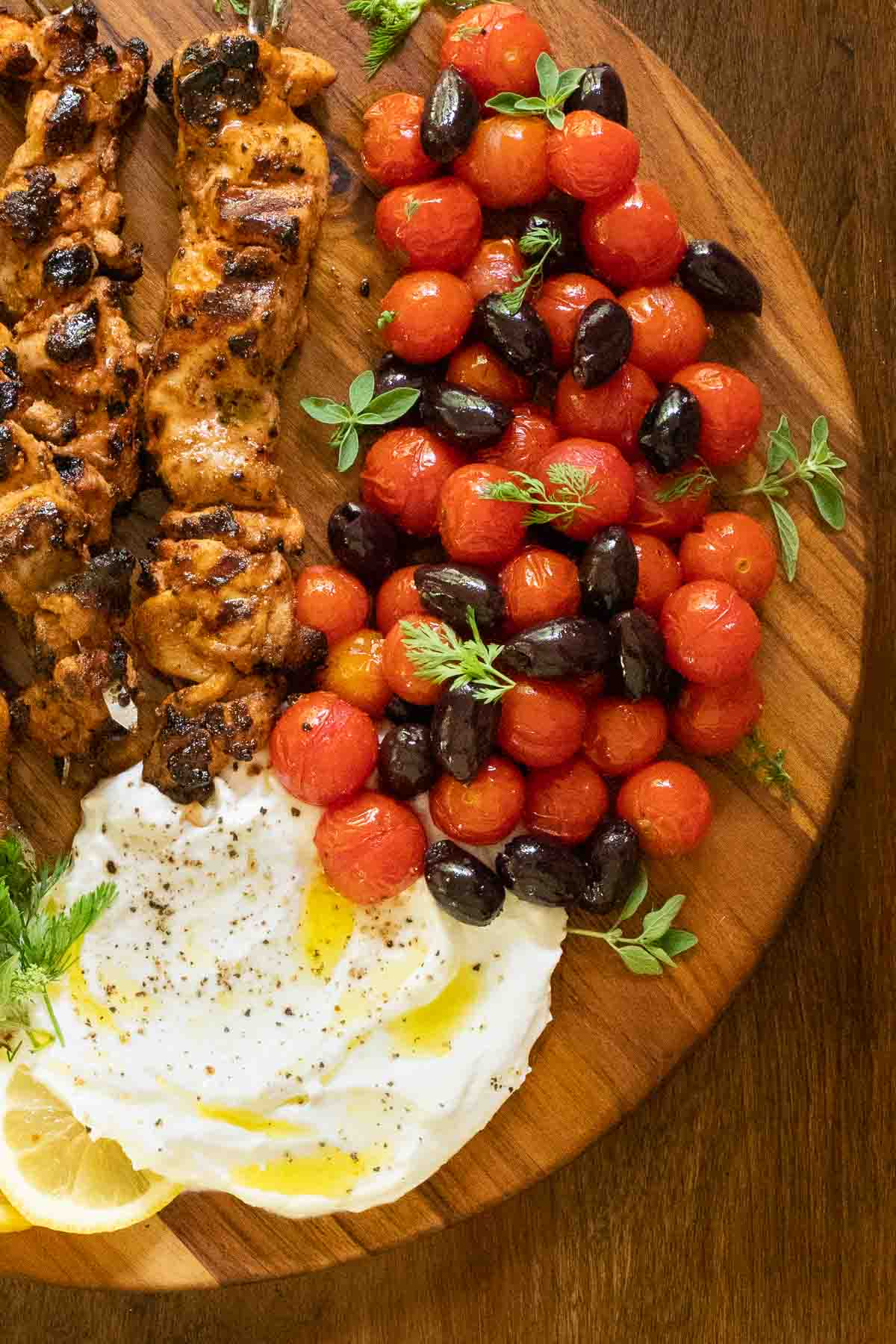 Overhead vertical photo of Middle Eastern Grilled Chicken with Toum (Shish Taouk) on a wood platter.