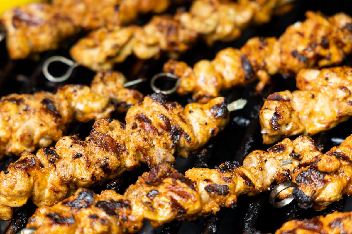Horizontal closeup photo of Middle Eastern Grilled Chicken on a barbecue grille.