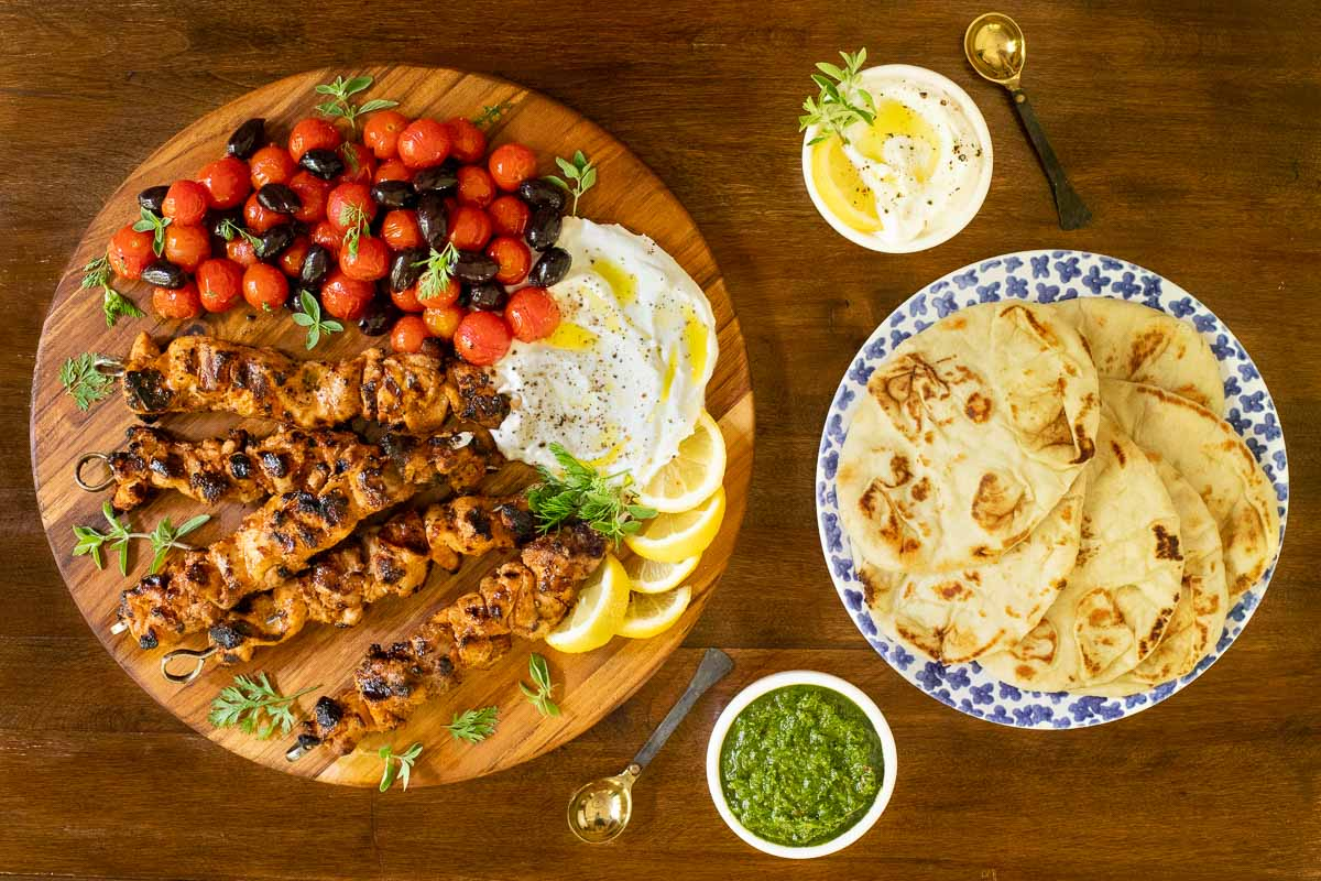 Overhead horizontal photo of Middle Eastern Grilled Chicken with Toum (Shish Taouk) on a wood platter and table.