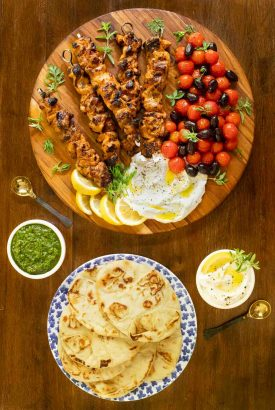 Vertical overhead picture of Middle Eastern Grilled Chicken on a platter with pita bread and sauces