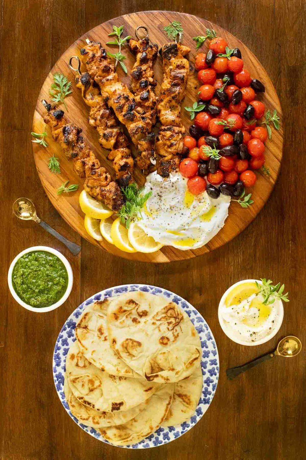 Vertical overhead photo of Middle Eastern Grilled Chicken on a platter with naan bread and sauces.