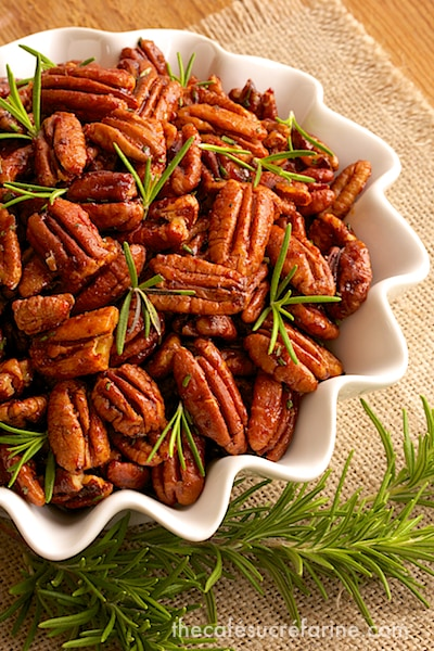 Overhead photo of a dish of Sweet and Spicy Roasted Pecans garnished with rosemary and positioned on a tan woven placemat.