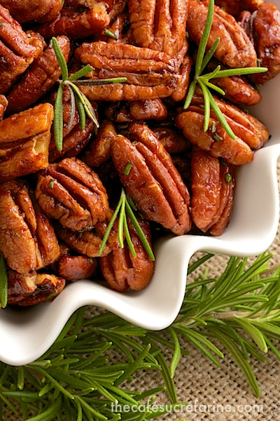 Closeup overhead photo of a dish of Sweet and Spicy Roasted Pecans garnished with fresh rosemary sprigs.