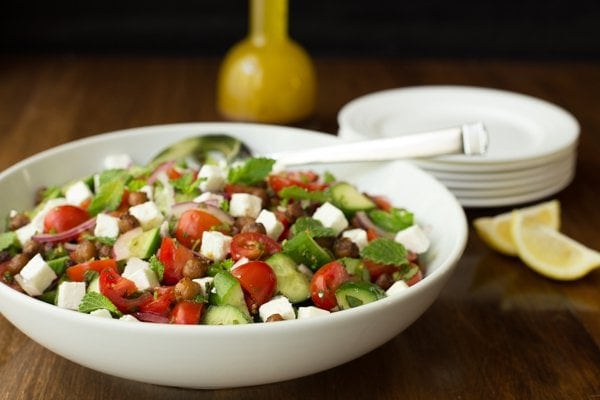 Horizontal image of Moroccan Tomato Cucumber Salad with Crispy Chickpeas in a white bowl with a cruet of dressing behind it.