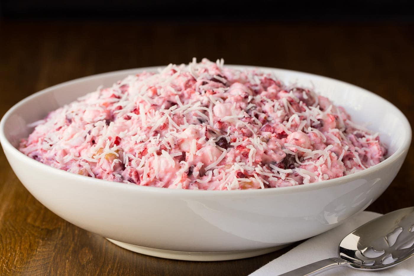 Photo of a white serving bowl of Nanny's Wonderful Cranberry Salad on a wood table.