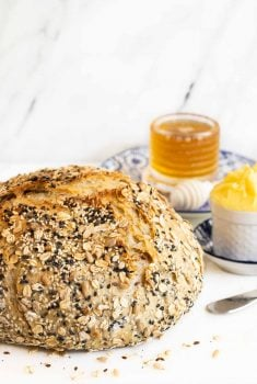 Vertical closeup photo of a loaf of No-Knead Seeded Oatmeal Bread with honey and butter on a white background.