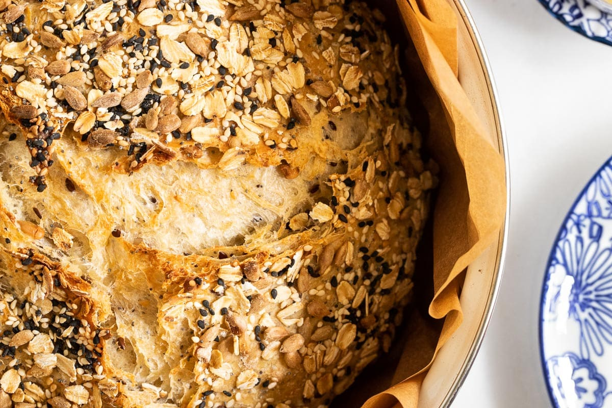 Closeup vertical overhead photo of a loaf of No-Knead Seeded Oatmeal Bread in a baking pot.
