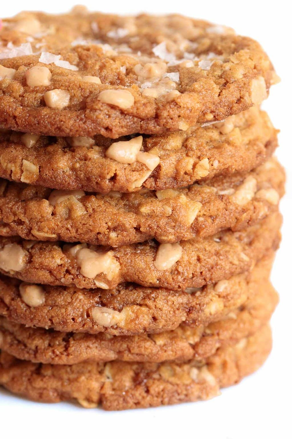 Close up vertical photo of a tall stack of Oatmeal Toffee Peanut Butter Cookies.