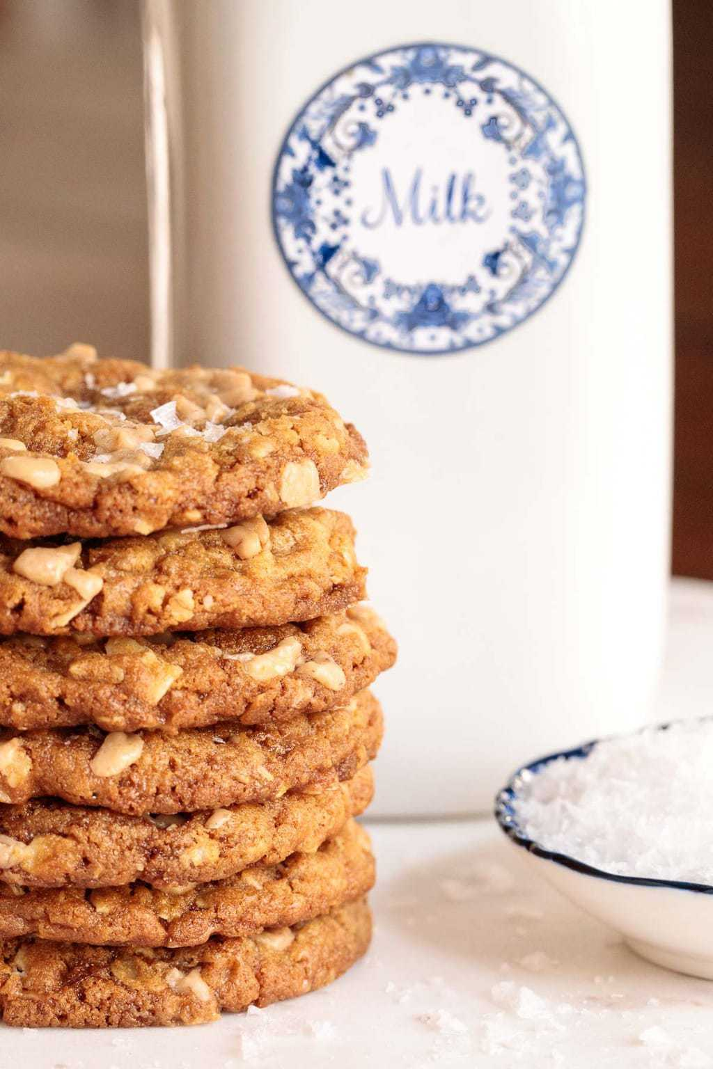 Closeup vertical photo of Oatmeal Toffee Peanut Butter Cookies on a marble surface with a glass quart of milk in the background.