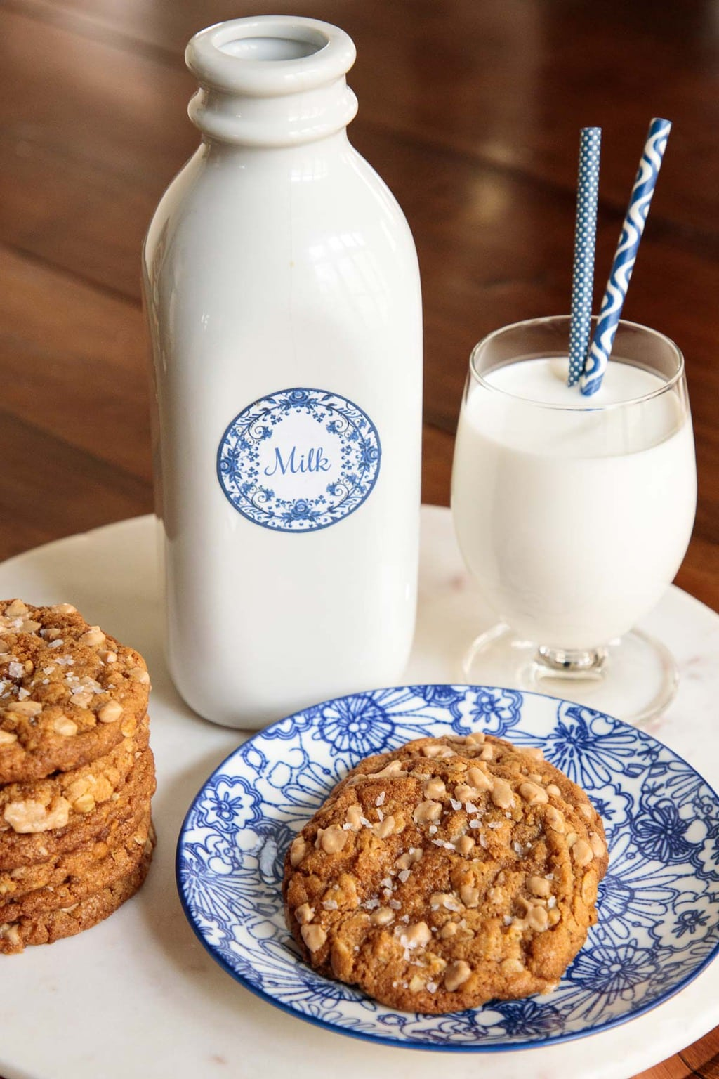 Photo of Toffee Oatmeal Peanut Butter Cookies on a white marble platter with a jug and a glass of milk in the background.
