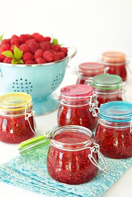 Horizontal photo of a table filled with Old Fashioned Raspberry Preserves in glass jars on turquoise napkins with a colander of fresh raspberries in the background.