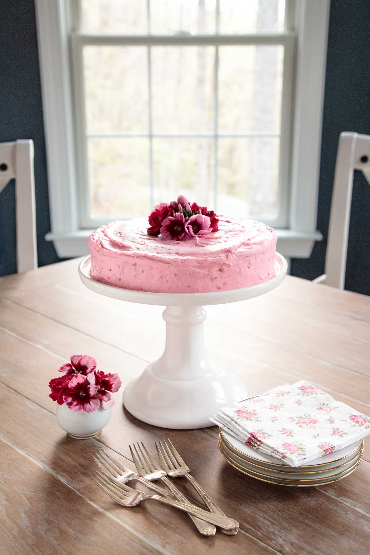 Long photo of a One-Bowl Buttermilk Cake with Raspberry Buttercream on a dining room table with a window and chairs in the background.