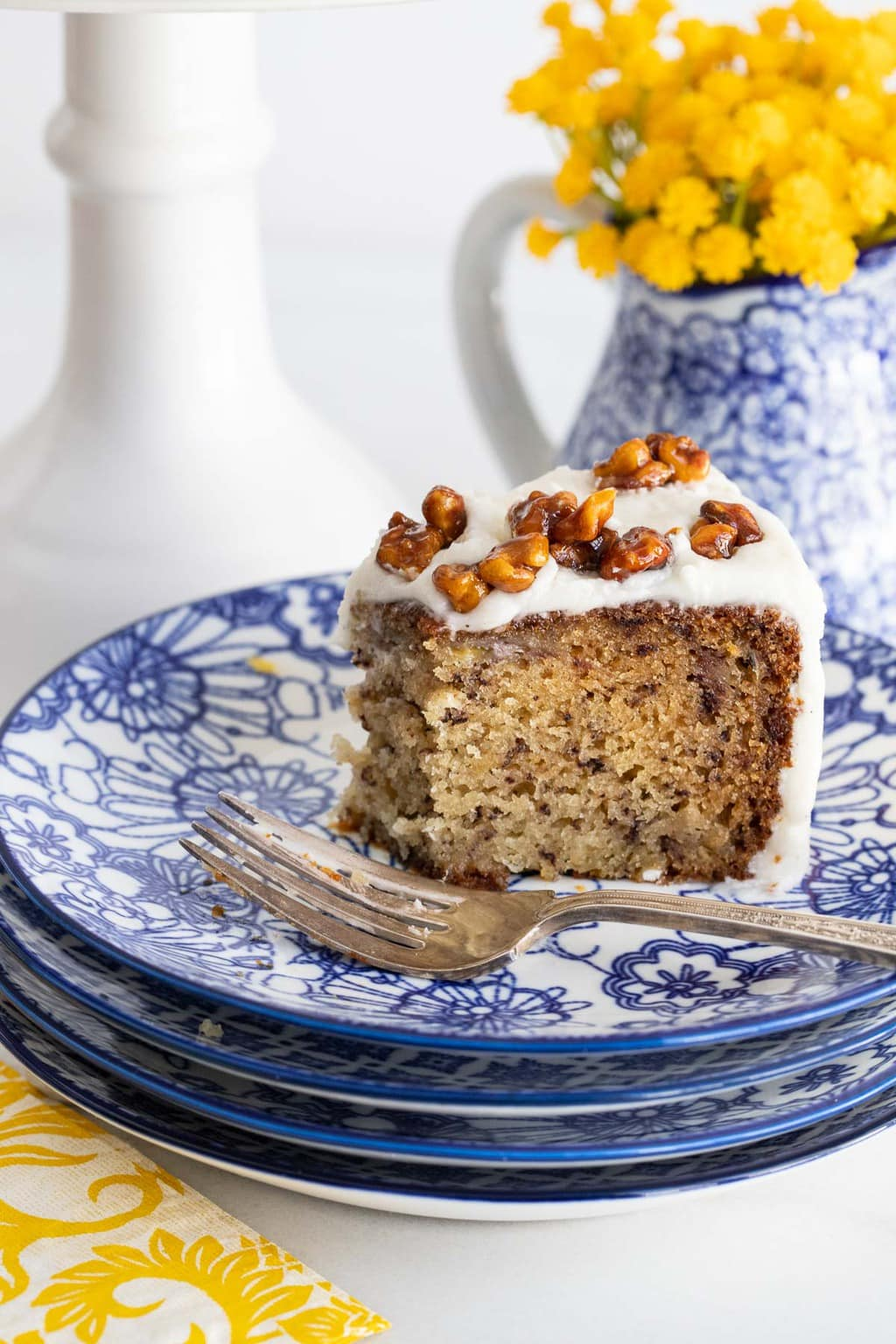 Photo of part of a slice of One-Bowl No-Mixer Banana Cake on a blue and white patterned serving plate.