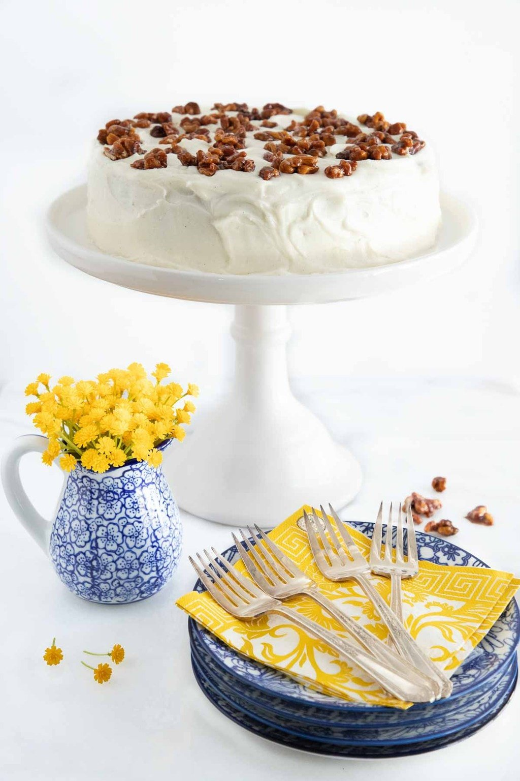 Photo of a One-Bowl No-Mixer Banana Cake on a white pedestal cake stand with serving utensils and dishes in the foreground.