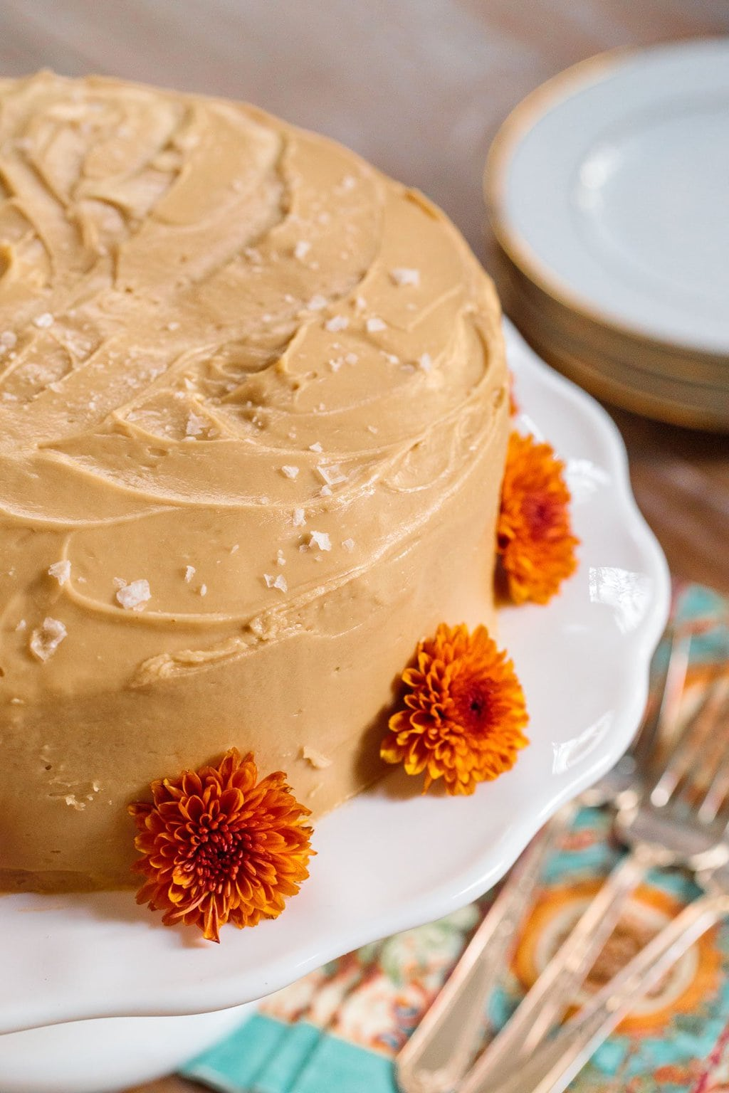 Photo of a One-Bowl Pumpkin Cake with Salted Caramel Icing on a white cake stand and decorated with deep orange chrysanthemums.