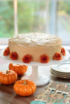 Vertical picture of one bowl pumpkin cake on a white cake stand, decorated with orange flowers and small pumpkins