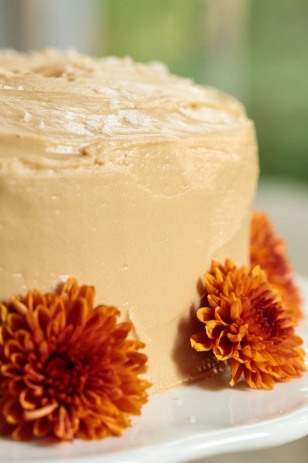 Closeup photo of the side of a One-Bowl Pumpkin Cake with Salted Caramel Icing decorated with deep orange chrysanthemums.