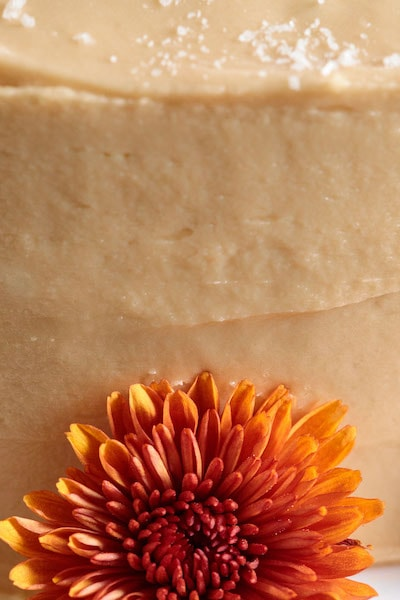 Closeup photo of the side of a One-Bowl Pumpkin Cake with Salted Caramel Icing featuring deep orange chrysanthemums.