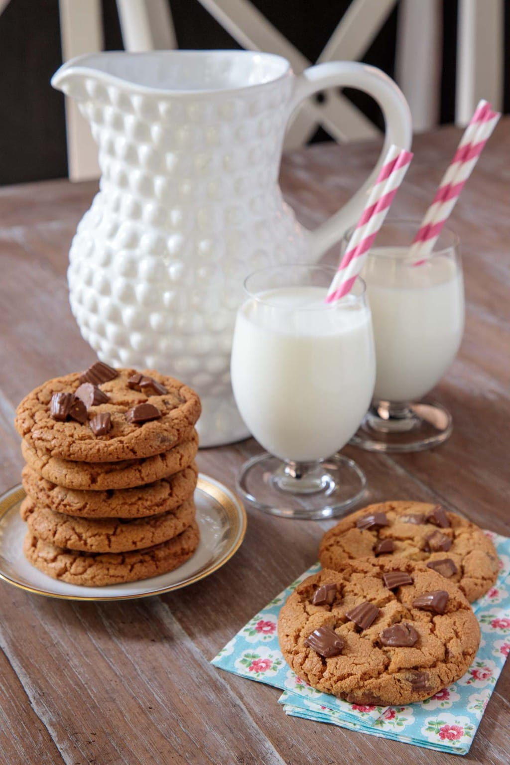 Vertical photo of One-Bowl Reese's Peanut Butter Cookies on a plate with glasses of milk and a pitcher in the background.