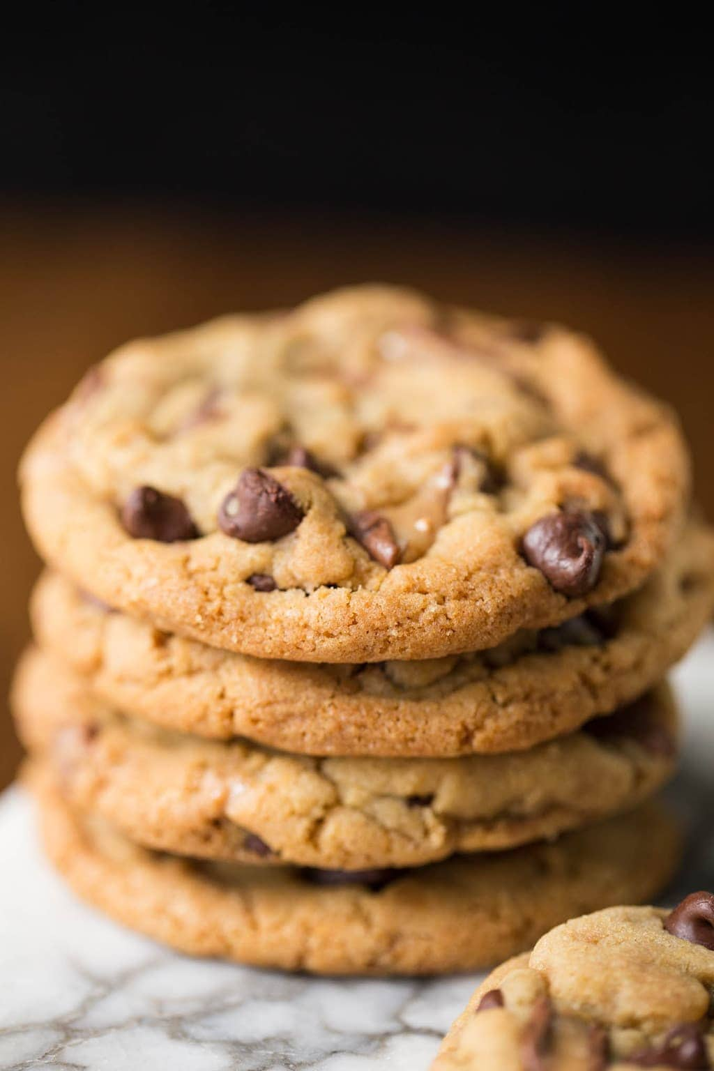 Vertical shot of a stack of One Bowl Toffee Bar Chocolate Chip Cookies on a marble slab.