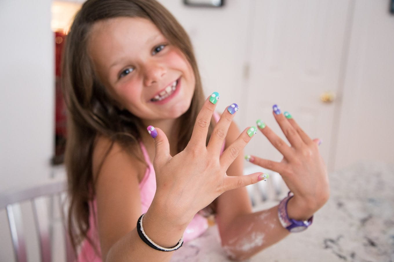A shot of a young girl baker showing off her brightly colored finger nails with flour on her arm from making cookies.