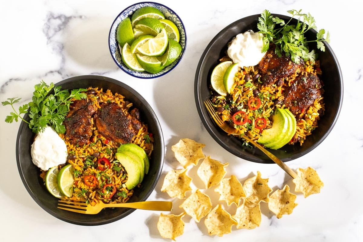 Horizontal overhead photo of two serving bowls of One-Pot Mexican Chicken and Rice with garnishes of tortilla chips and lime wedges.