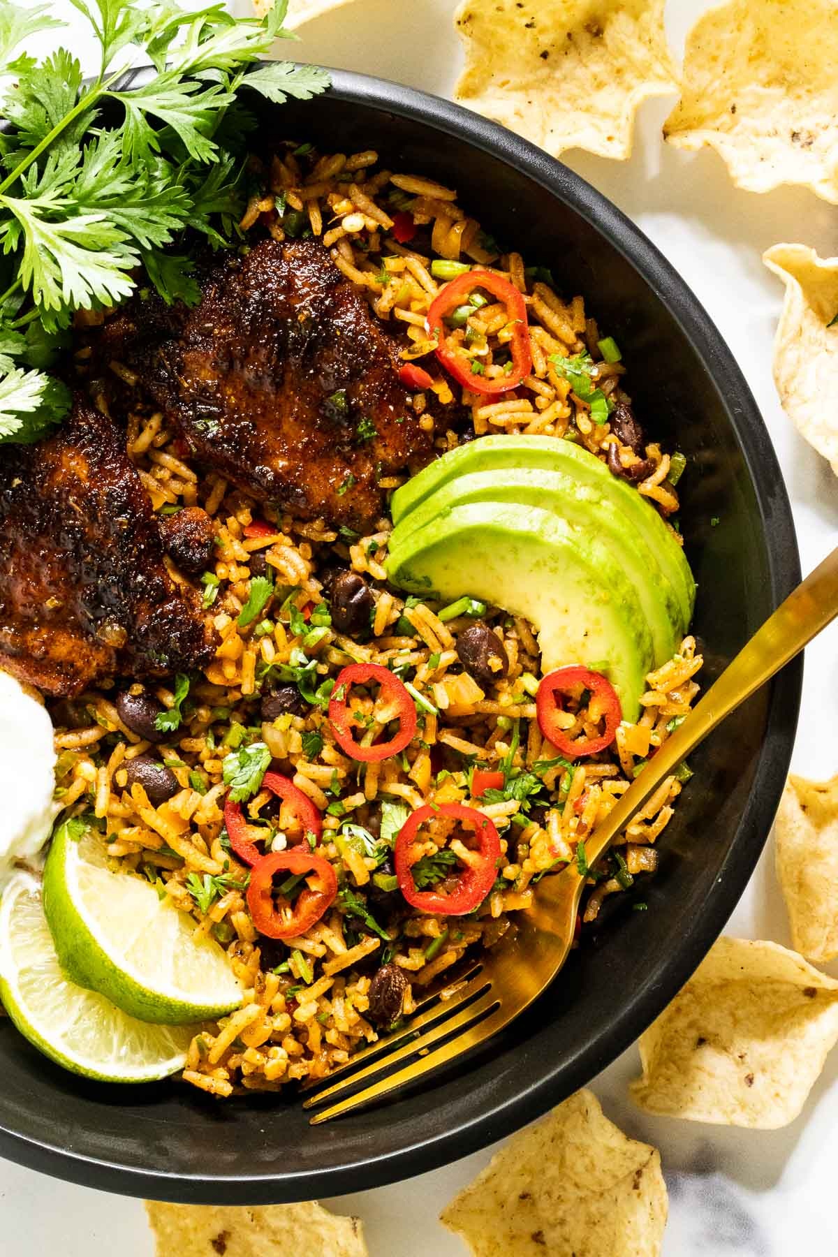 Vertical overhead closeup photo of One-Pot Mexican Chicken and Rice in a black serving bowl garnished with avocado slices, slice red peppers, cilantro and lime wedges and surrounded with tortilla chips.